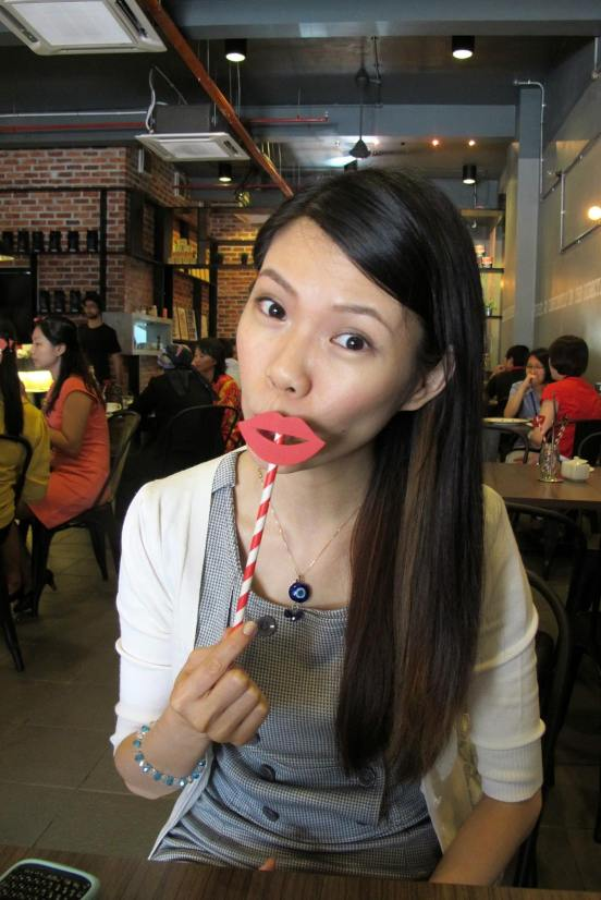 Mei Sze playing around with the props on the table. Lips for girls, moustache for guys!