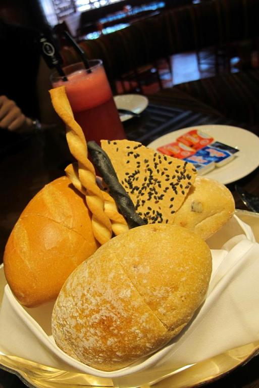 A bread basket filled with soft, fluffy and delicious breads and breadsticks!