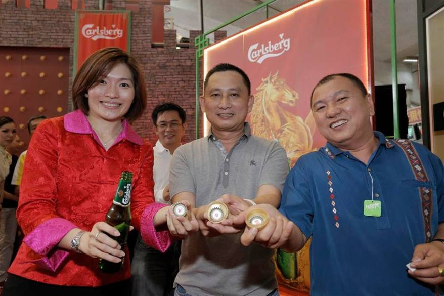 Carlsberg Marketing Director Juliet Yap showing off the bottle caps with the ang pau prizes. Make sure you don't simply throw the bottle caps away without checking first!