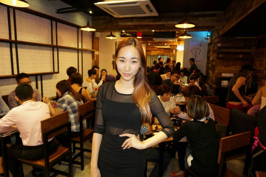 Radio DJ Melissa Thng inside the outlet. The interior of the outlet is a mix of dark wood and white walls with tables for dining as well as a couple of sofas for lounging.