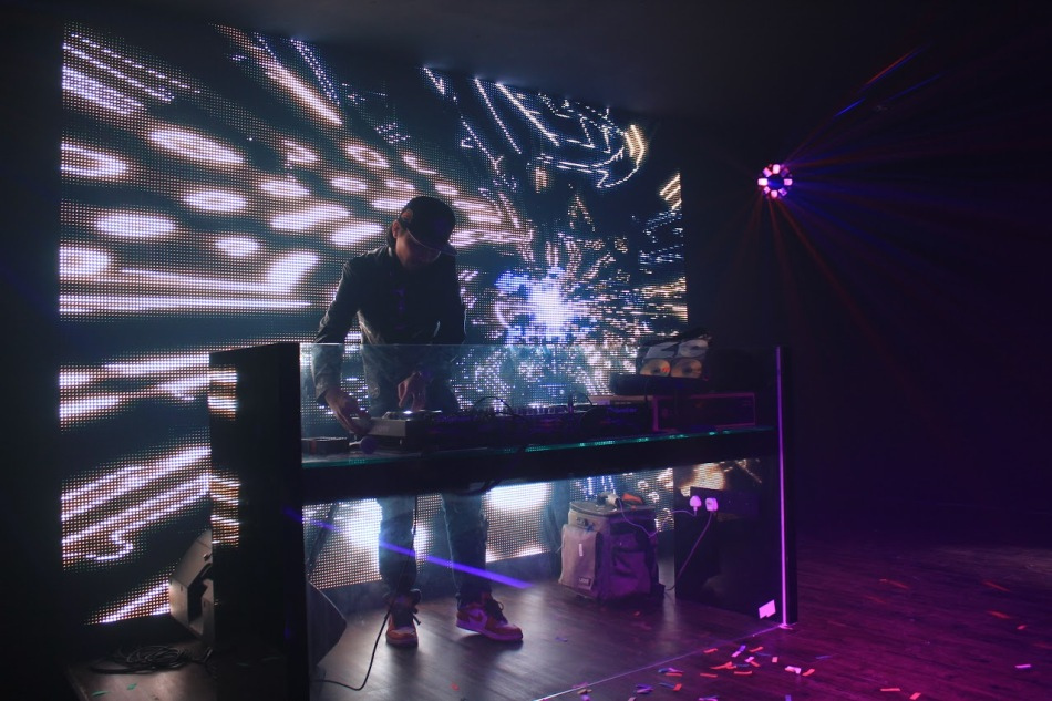 The DJ console is located on the stage behind the runway