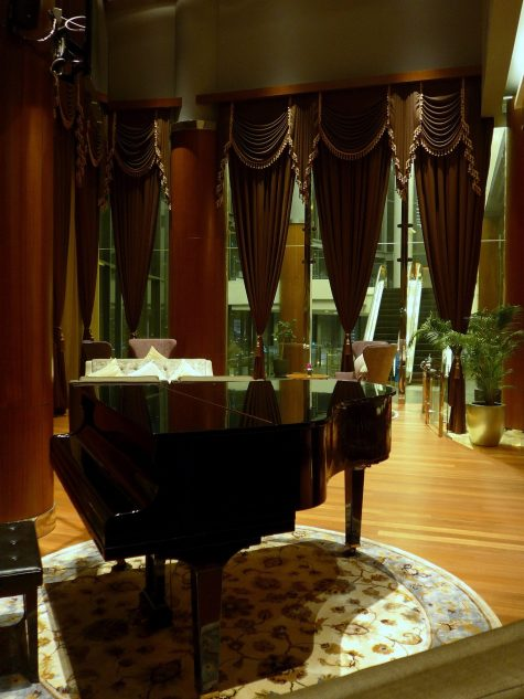A baby grand piano in the lounge section