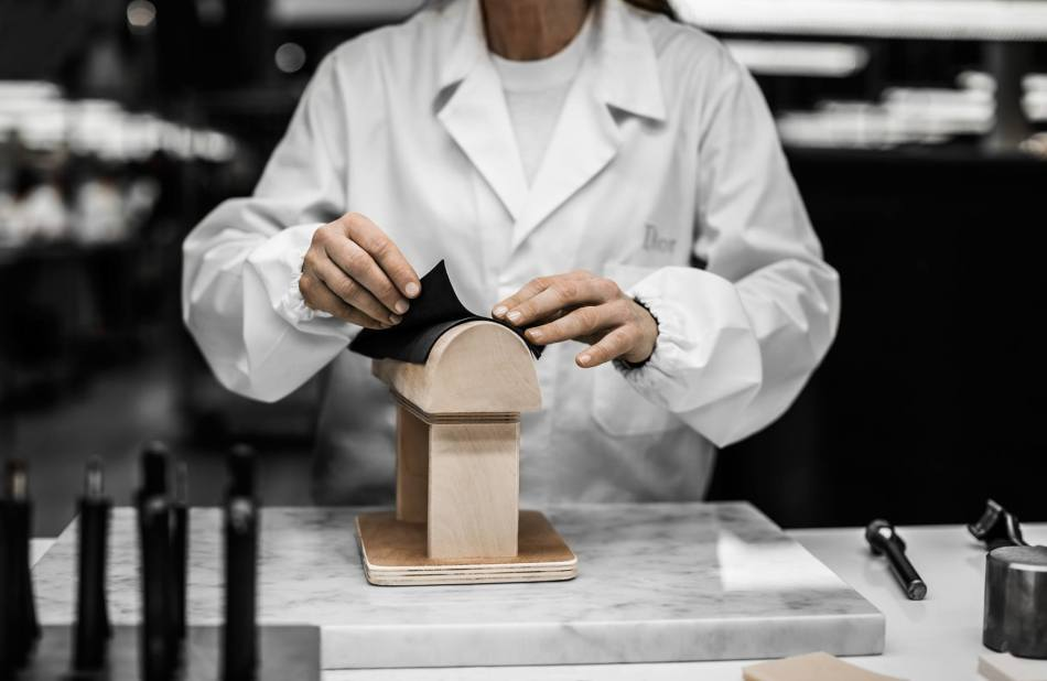The craftsman shapes the bag's leather sides on a wooden form made by the modelmaker according to the bag's materials and dimensions.