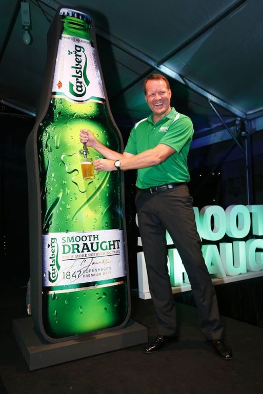 Henrik Andersen, Managing Director of Carlsberg Malaysia tapping a glass of Carlsberg Smooth from the giant bottle
