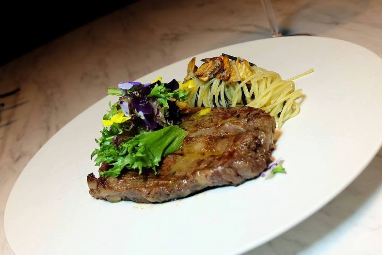 Wagyu MB9 -Wagyu Marbling 9 butter seared and served with Aglio Olio Pasta, Mesclun and Herbed Balsamic Aged Vinaigrette -RM288