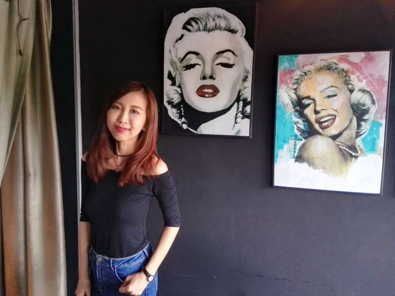 My partner with some paintings of Marilyn Monroe