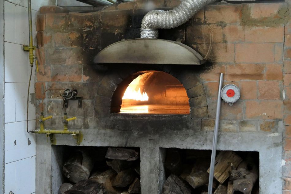 A wood fired oven burns bright in the kitchen