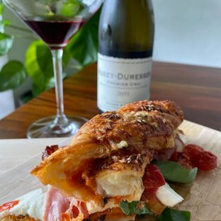 """Italian """"Caprese"""" sandwich with veal bacon. Flaky tomato-olive pastry sandwiched with fresh buffalo mozzarella, Piennolo cherry tomatoes from Campania, premium veal bacon and italian sweet basil"""