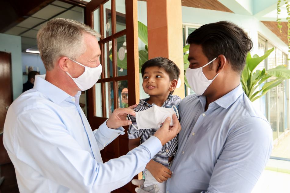Kyle Pretorius, Shangri-La Hotel, Bangkok helping put on Niroshan's son's mask at Cedar Learning Center (CLC), Bangkok